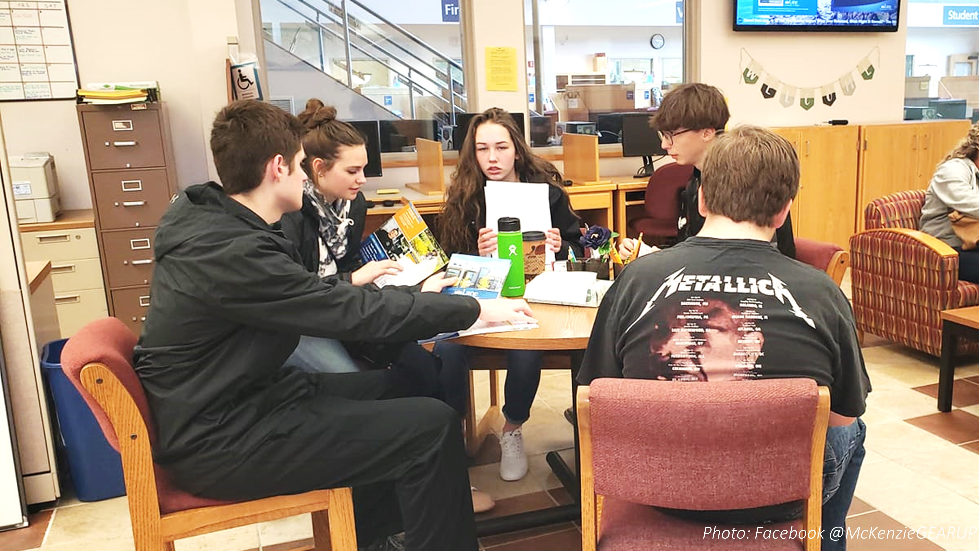 students sit around a table looking at college brochures