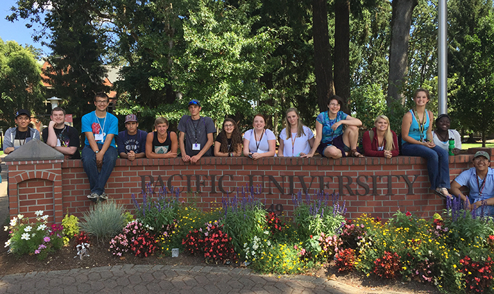 College App Camp students sitting on Pacific University sign